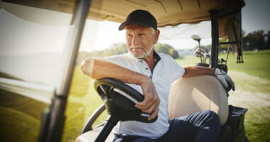Smiling senior man sitting in a golf cart looking out at the fairway while playing a round of golf on a sunny day